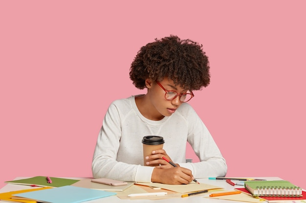 ピンクの壁に向かって机でポーズをとって焦点を当てた学生の女の子