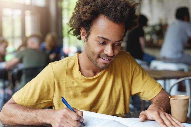大学の食堂でコーヒーを飲みながら座っている間、彼のノートに何かを書くカジュアルなtシャツを着て、暗いふさふさした髪と剛毛を持つ集中した学生男性。ハンサムなスタイリッシュな男の概要を書く