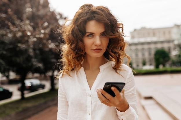Сосредоточенная стильная женщина с вьющимися волосами, отправляющая текстовое сообщение в осенний день, милая женщина, идущая мимо зеленых кустов с улыбкой