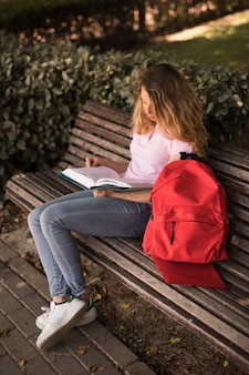 Focused teen woman reading workbook on bench