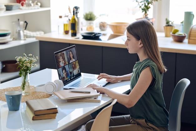 Сосредоточенная девочка-подросток сидит за столом и использует ноутбук, улучшая навыки в онлайн-классе репетиторства