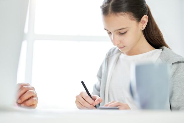 집에서 아버지와 시간을 보내는 동안 무언가를 그리는 데 집중한 10대 라틴 소녀. 잠금, 가족 개념 동안 온라인 공부. 선택적 초점
