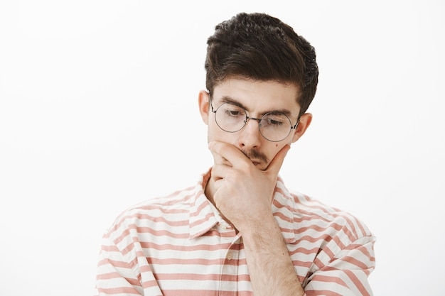 Focused thinking male program developer in trendy glasses, tilting head down and touching chin, being concerned while making decision or planning something over gray wall