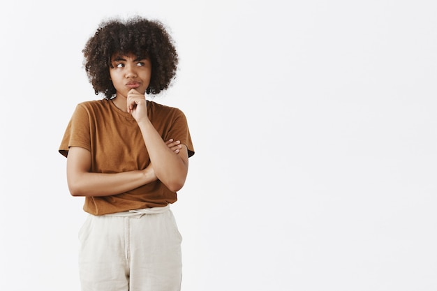 Focused thoughtful cute girl with afro hairstyle in brown t-shirt and pants smirking looking right while thinking with doubts