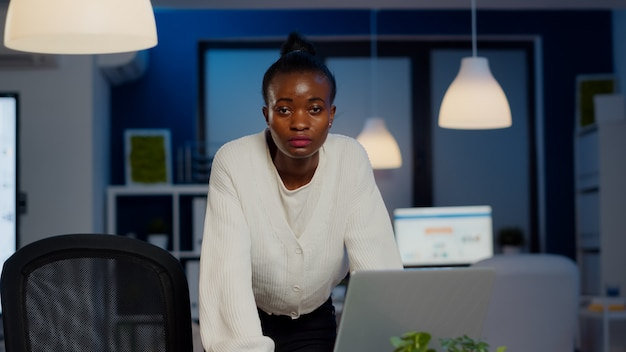 Focused tired business woman looking at front after reading tasks on laptop standing near desk in start-up company late at night