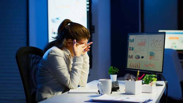 피곤한 기업가가 사무실 초과 근무에서 노트북에 쓰는 노트북에서 그래픽을 확인하는 데 집중했습니다. 현대 기술 네트워크 무선 읽기 타이핑, 검색을 사용하는 바쁜 직원