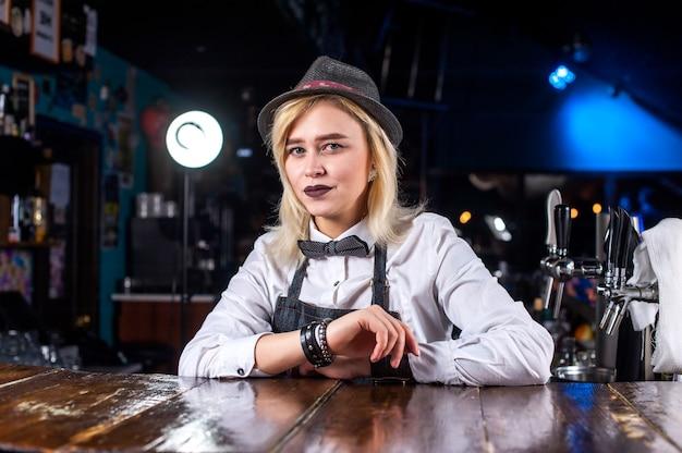 Сосредоточенная женщина-бармен устраивает шоу, создавая коктейль за барной стойкой