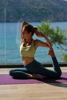 Focused woman doin yoga in mermaid pose on terrace