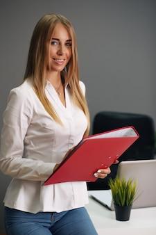 Сосредоточенная женщина, держащая красную папку