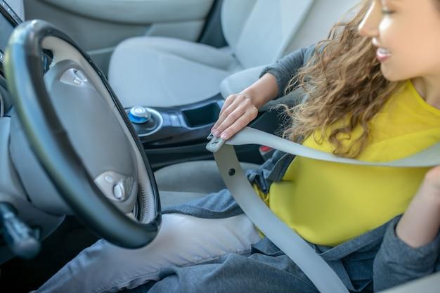 新しい車のシートベルトを締めて運転席に焦点を当てた女性