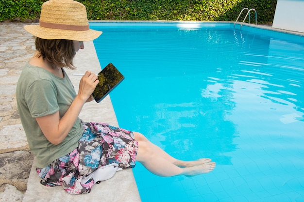 Сосредоточенная женщина в соломенной шляпе, сидящая у бассейна