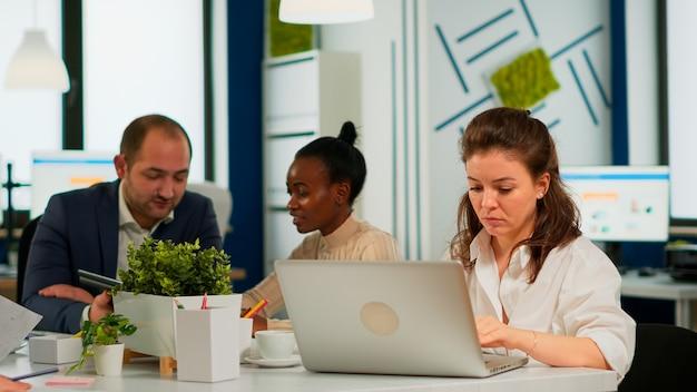 ラップトップで入力し、机に座ってインターネットを閲覧し、マルチタスクを集中して行う集中的な女性マネージャー。現代のオフィスでスタートアップ金融会社について話している多民族の同僚。