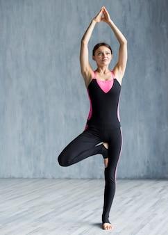 Сосредоточенная женщина практикует йогу в позе дерева