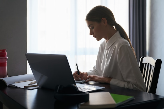 Focused woman sitting at table and working on laptop