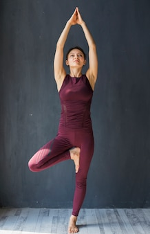 Focused woman standing in a tree pose with arms extended above her