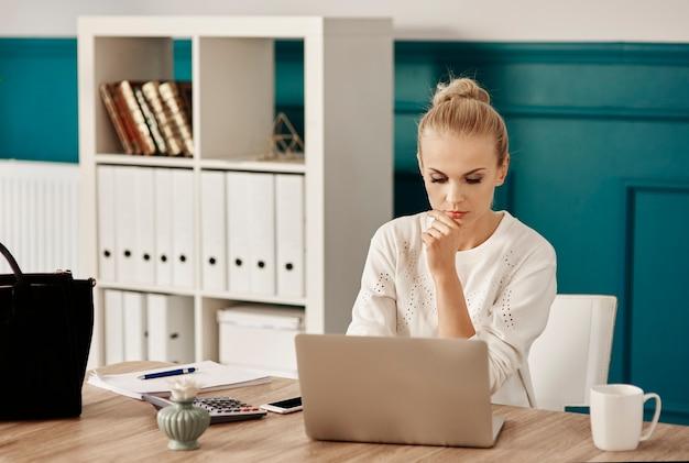 ホームオフィスでラップトップを使用して焦点を当てた女性