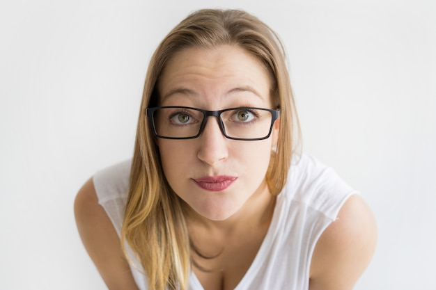 Focused woman wearing glasses and staring at camera