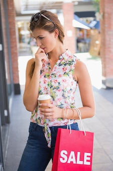 선글라스, 갈 커피와 쇼핑백 집중된 여자