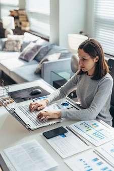 Focused woman working from home office on laptop.