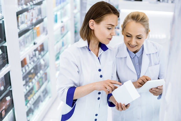 Focused women pharmacists standing in front of a glass case in a pharmacy holding a tablet, checking