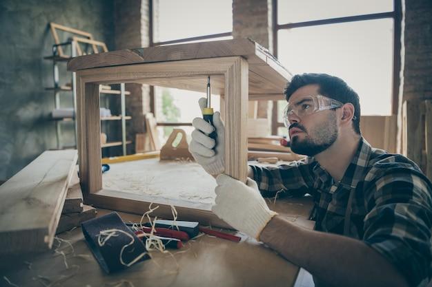 Сосредоточенный рабочий в своем доме, дома, гараже, ремонт деревянных плит, стол, использует отвертку, сверла, винты, надевает защитные очки, перчатки