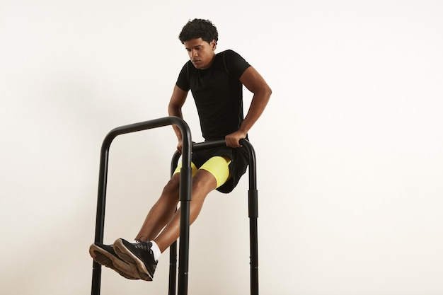 Focused young african american athlete in black sportswear performing bodyweight rows on mobile bars isolated on white