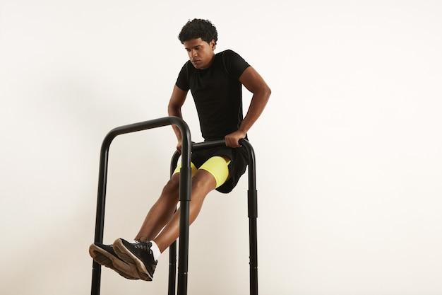 Focalizzato giovane atleta afroamericano in abiti sportivi neri eseguendo righe a peso corporeo su barre mobili isolate su bianco