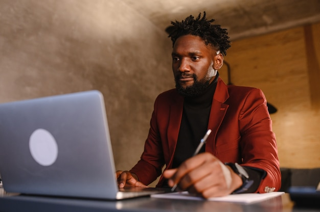 Focused young african businessman wear headphones study online watching webinar podcast on laptop
