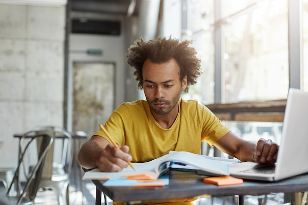 Сосредоточенный молодой афро-американский учитель английского языка проверяет тетрадки своих учеников, сидя за столиком в кафе перед открытым портативным компьютером. серьезный темнокожий студент учится на уроке в университетской столовой