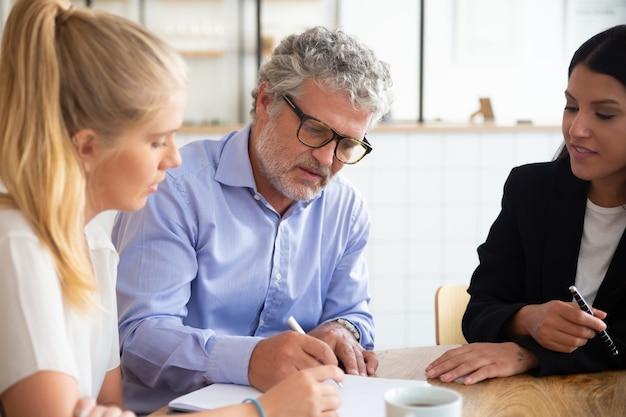 중개인과 만나 보험 계약에 서명하는 집중된 젊고 성숙한 고객