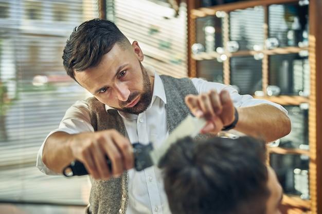 それをトリミングしながら彼のクライアントの髪を注意深く見ている集中した若い床屋