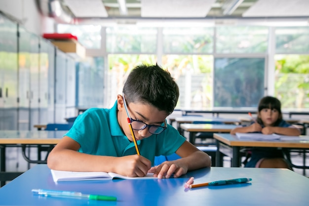 Focused young boy in glasses sitting at desk and writing in copybook in class