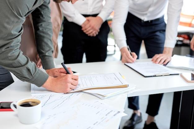 同僚とのオフィスで契約に署名する焦点を絞った青年実業家。正装のトリミングされた男は、ビジネスの会議の議論の後の会議で紙の契約書に署名を書きます