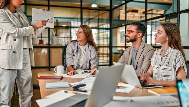 현대 사무실에서 노트북 테이블에 앉아 동료의 그룹 종이에 그래프를 보여주는 젊은 백인 비즈니스 여자를 집중.