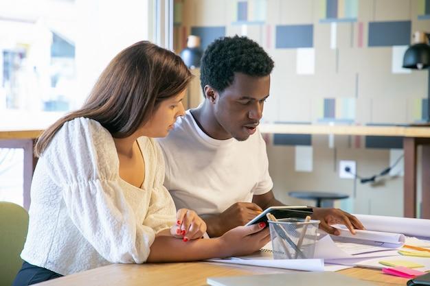Focalizzato giovani designer guardando i progetti e lo schermo del tablet, seduti a tavola, lavorando insieme e parlando
