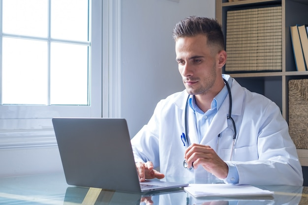 Focused young doctor wearing glasses working on laptop in office, sitting at desk, looking at screen, serious therapist gp writing report or email, consulting patient online, filling medical card