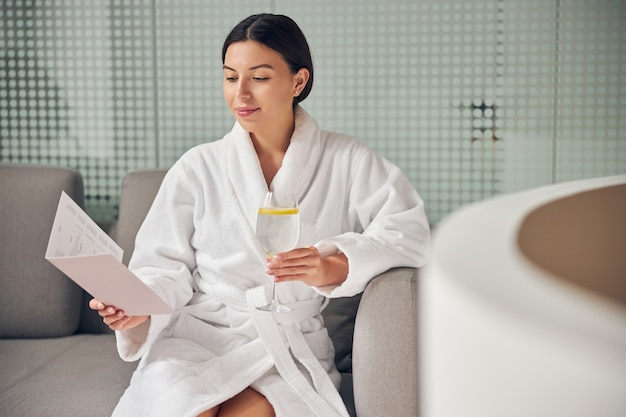 Сосредоточенная молодая клиентка смотрит на прайс-лист услуг в брошюре о спа