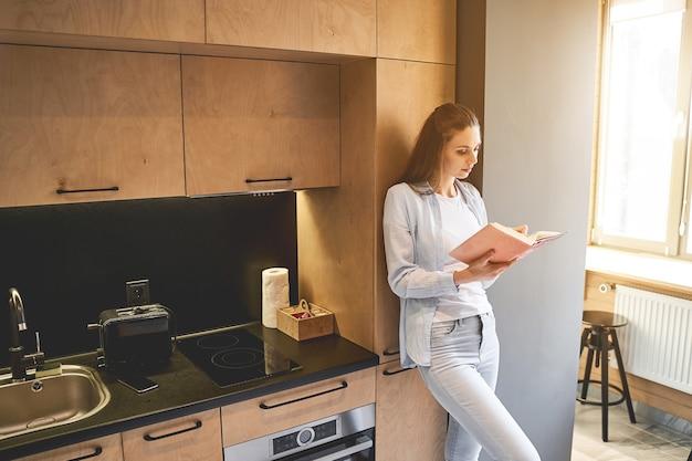 요리 책에서 새로운 요리법을 찾는 긴 머리를 가진 집중된 젊은 여성 요리사