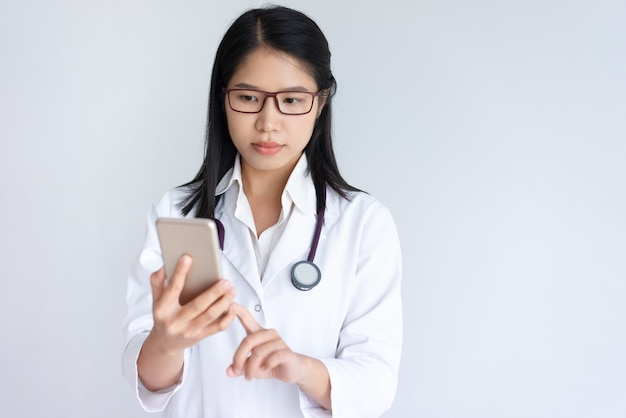 Focused young female doctor using smartphone