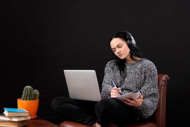 自宅からリモートでオンラインで作業するラップトップとヘッドフォンで座っている焦点を当てた若いフリーランスの女性