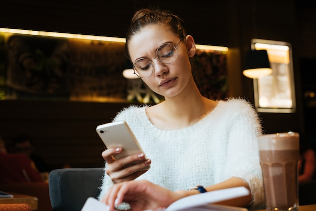 Focused young girl freelancer in glasses works, holds a smartphone, in a cafe