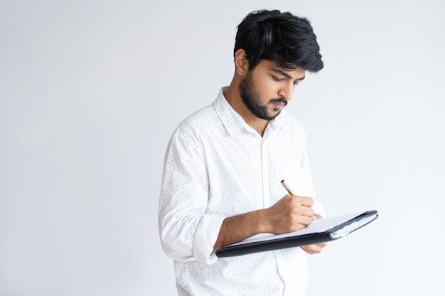 Focalizzato giovane ragazzo indiano tenendo il file e la scrittura. lavoro uomo d'affari.