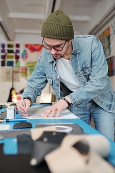 Focused young man in denim outfit tracing sewing patterns on leather fabric in workshop
