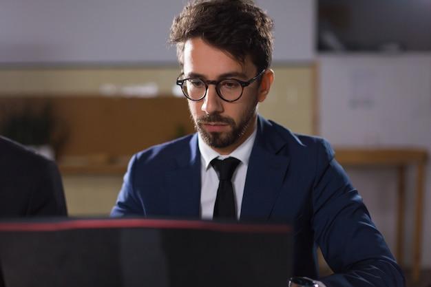 Focused young man in eyeglasses looking at laptop