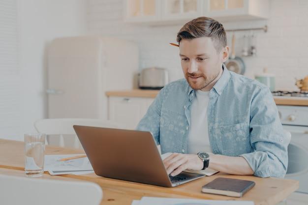 Сосредоточенный молодой человек-фрилансер, использующий ноутбук во время работы из дома на своем рабочем месте, молодой человек, печатающий на ноутбуке и серфинг в интернете, глядя на экран, сидя за кухонным столом