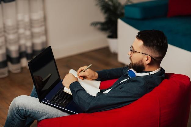 Focused young man wear headphones and eyeglasses study online watching webinar on laptop. he make notes in notebook.