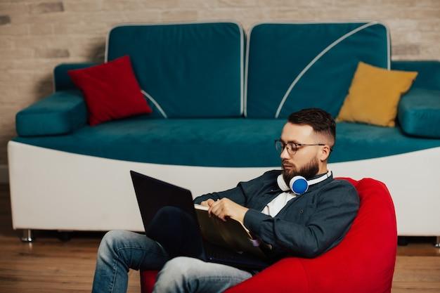 Сосредоточенный молодой человек в наушниках учится онлайн, смотрит веб-семинар на ноутбуке или учебный курс и делает заметки.