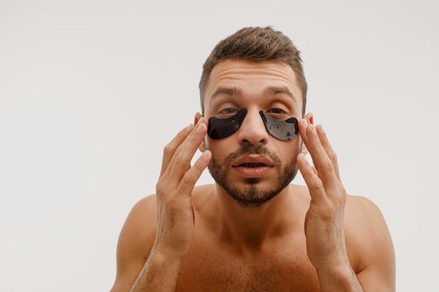 Сосредоточенный молодой человек с повязкой на глазу на лице. бородатый парень с идеальной кожей смотрит в камеру. концепция ухода за кожей лица. изолированные на белом фоне. студийная съемка. копировать пространство