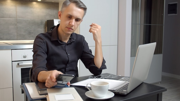 自宅のキッチンに座ってラップトップで作業し、スマートフォンを使用して焦点を当てた若い男