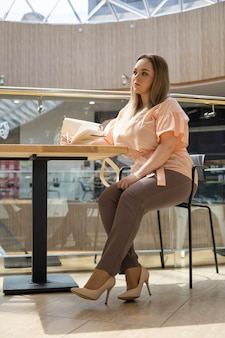 집중된 젊은 플러스 사이즈 비즈니스 여성이 사무실 내부 테이블에 앉아 휴대폰을 사용하여 채팅